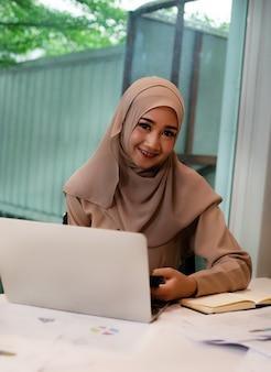 La mujer de negocios haciendo papeleo, en la sala de reuniones, con sentimiento feliz