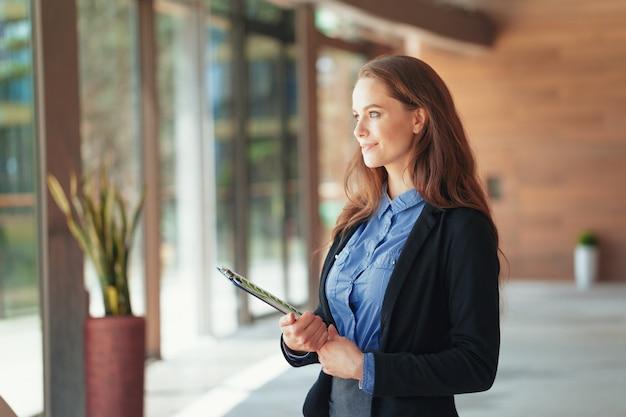 Mujer de negocios hermosa feliz con el tablero en la oficina.