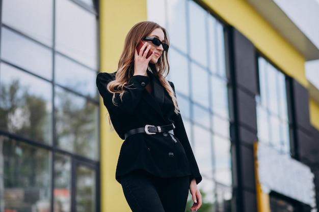 Mujer de negocios hermosa joven por el centro de la oficina, usando el teléfono