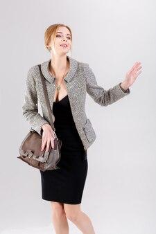 Mujer de negocios hermosa joven rubia en vestido negro, chaqueta y bolso ondeando sobre fondo gris