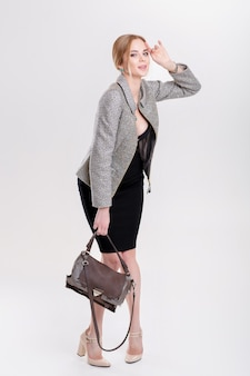 Mujer de negocios hermosa joven rubia en vestido negro, chaqueta y bolso smilling sobre fondo gris