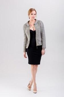 Mujer de negocios hermosa joven rubia en vestido negro, chaqueta sobre fondo gris