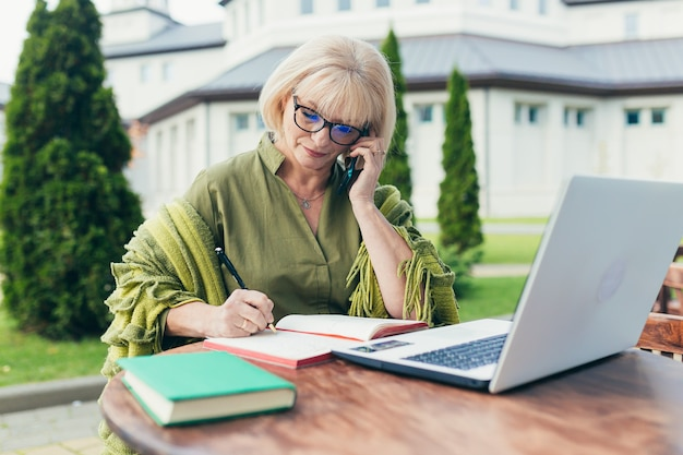 Mujer de negocios hermosa senior sentada en una silla y tomando notas en un cuaderno con un teléfono