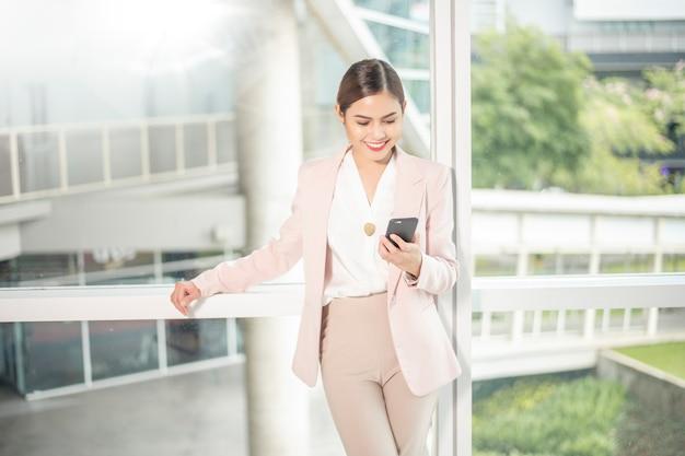 La mujer de negocios hermosa está utilizando el teléfono elegante para el negocio