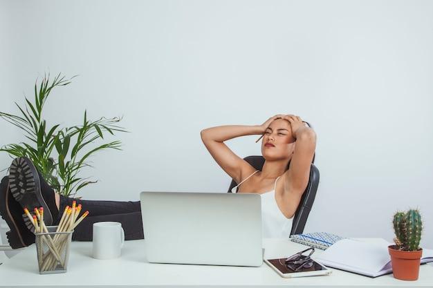 Mujer de negocios jove con dolor de cabeza descansando