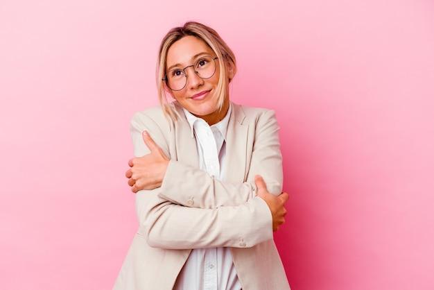 Mujer de negocios joven aislada en abrazos de pared rosa, sonriendo despreocupada y feliz