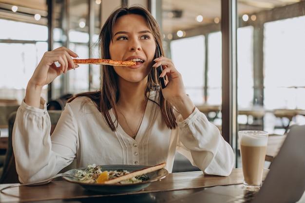 Mujer de negocios joven almorzando en un café y trabajando en equipo