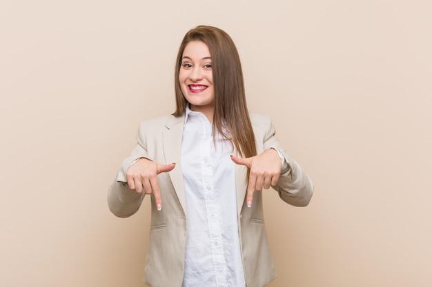 Mujer de negocios joven apunta hacia abajo con los dedos, sentimiento positivo.