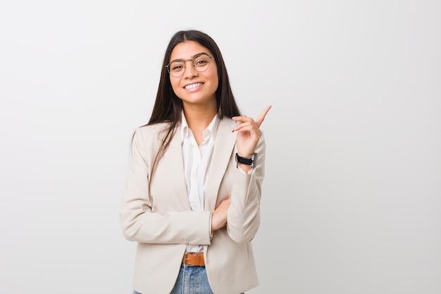 Mujer de negocios joven árabe aislada contra una pared blanca sonriendo alegremente señalando con el dedo lejos.