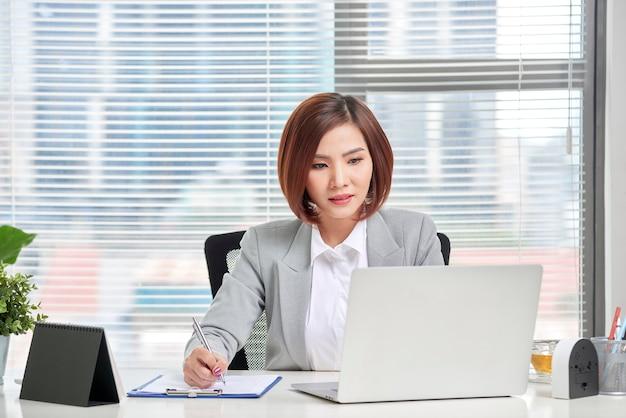 Mujer de negocios joven, atractiva y segura que trabaja en la oficina