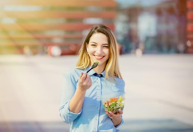 Mujer de negocios joven con la caja de almuerzo de la ensalada en al aire libre