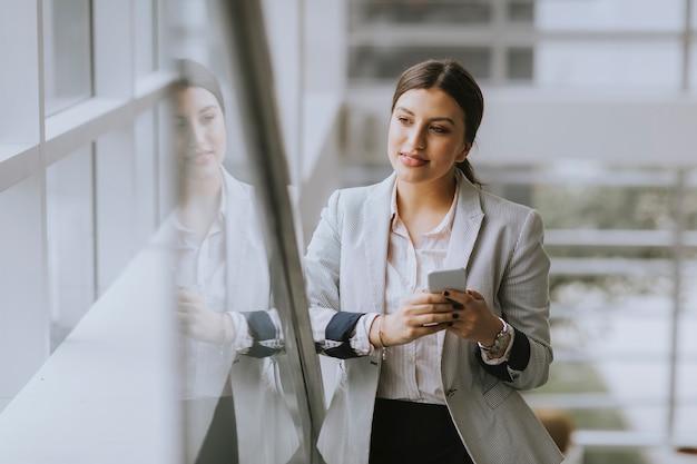 La mujer de negocios joven se coloca en las escaleras en la oficina y utiliza el teléfono móvil