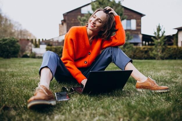 Mujer de negocios joven con la computadora portátil en la hierba