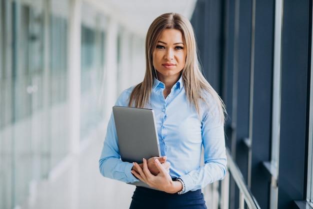 Mujer de negocios joven con la computadora portátil que se coloca en una oficina