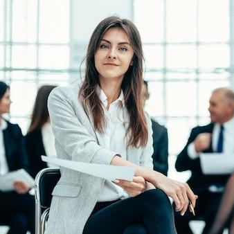 Mujer de negocios joven en el contexto de sus colegas