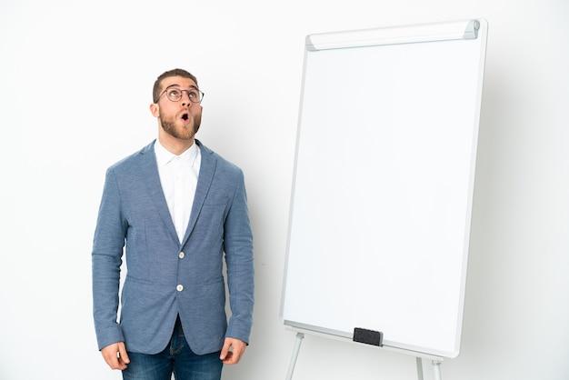 Mujer de negocios joven dando una presentación en tablero blanco aislado