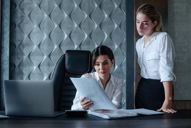 Mujer de negocios joven directora sentada en el escritorio de oficina con documentos de proceso de trabajo reunión de negocios trabajando con un colega para resolver tareas comerciales concepto colectivo de oficina