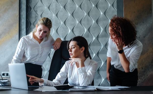 Mujer de negocios joven directora sentada en el escritorio de oficina usando computadora portátil proceso de trabajo reunión de negocios trabajando con colegas para resolver tareas de negocios concepto colectivo de oficina