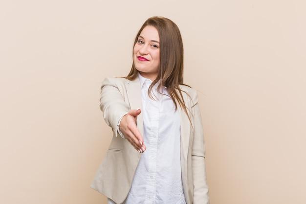 Mujer de negocios joven estirando la mano en gesto de saludo.