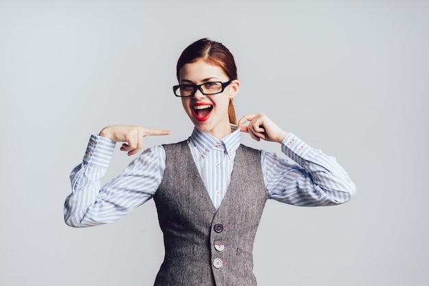 Mujer de negocios joven con gafas se ríe alegremente, mira a la cámara. aislado en un fondo gris