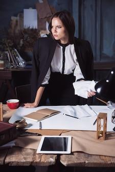 Mujer de negocios joven garabateando documentos en la cámara