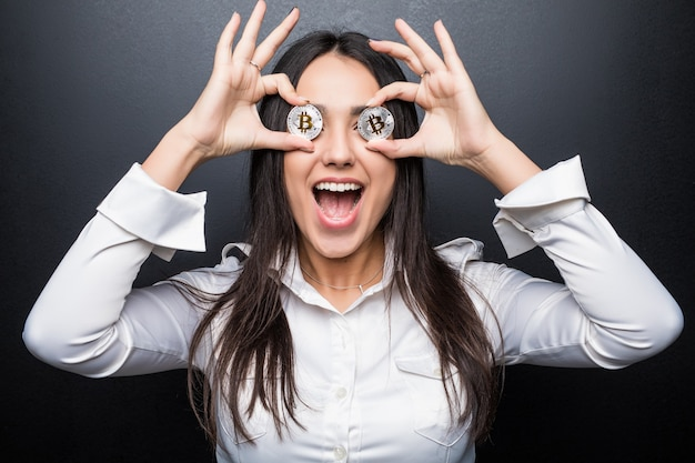 Mujer de negocios joven grito cubrir los ojos con bitcoin aislado en la pared negra