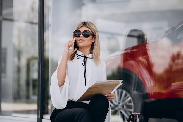 Mujer de negocios joven hablando por teléfono y leyendo documentos