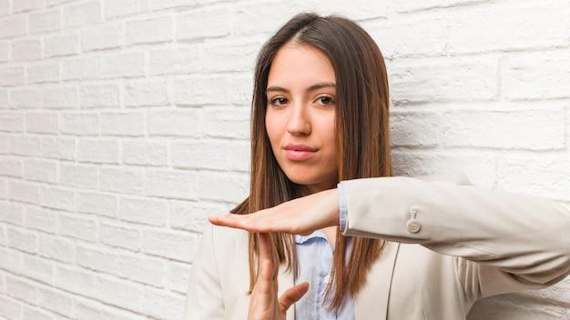 Mujer de negocios joven haciendo un gesto de tiempo de espera