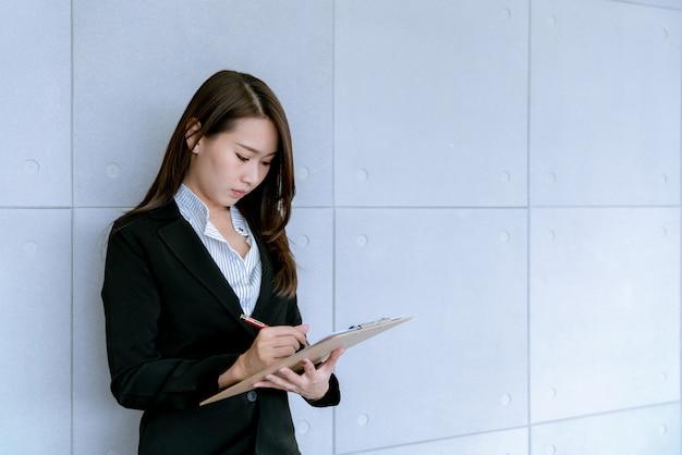 Mujer de negocios joven hermosa asiática en falda del traje usando documento de trabajo sobre ventas y plan de comercialización