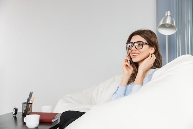 Mujer de negocios joven hermosa que se sienta en un sofá en la oficina, hablando por teléfono móvil