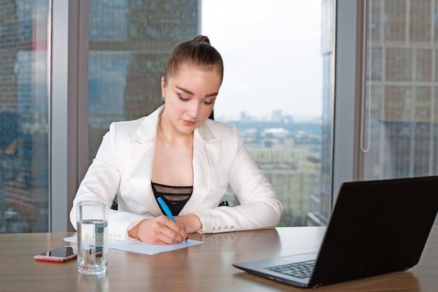 Mujer de negocios joven inválida o discapacitada persona sentada en silla de ruedas trabajando en la oficina en una computadora portátil