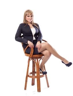 Mujer de negocios joven en un juego, sentándose en taburete de barra.