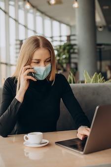Mujer de negocios joven en máscara trabajando en equipo portátil en un café