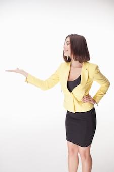 Mujer de negocios joven mostrando algo sobre el fondo blanco.