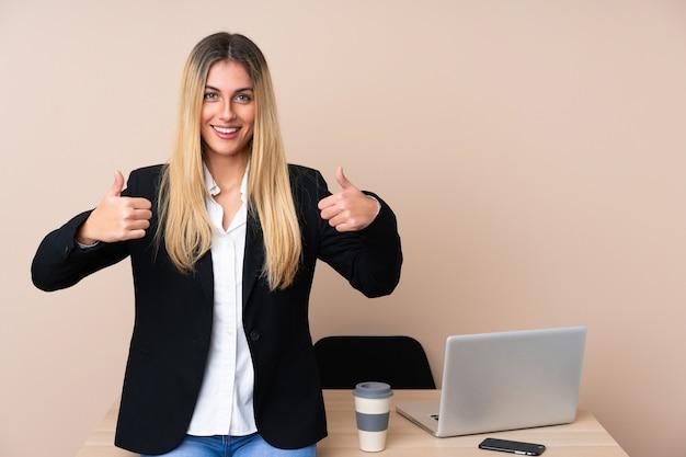 Mujer de negocios joven en una oficina dando un gesto de pulgares arriba
