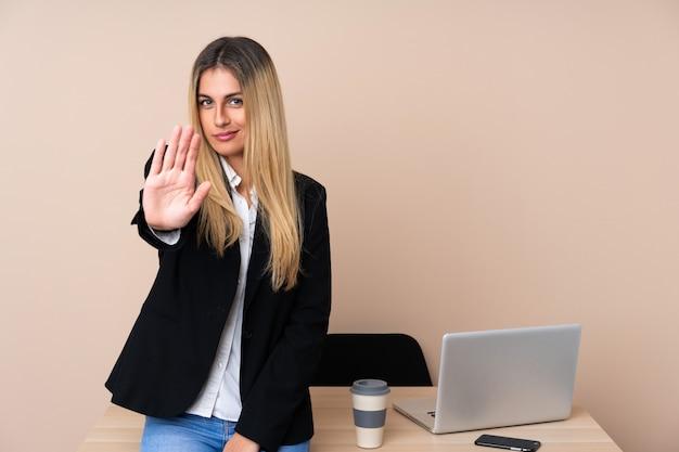 Mujer de negocios joven en una oficina haciendo gesto de parada con la mano