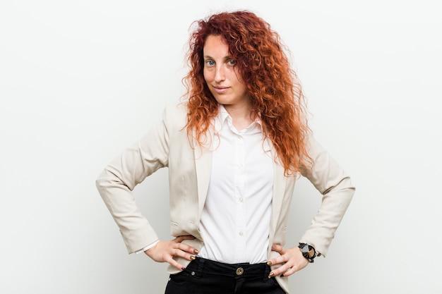 Mujer de negocios joven pelirroja natural contra la pared blanca confía en mantener las manos en las caderas.