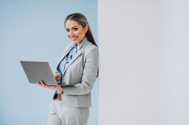 Mujer de negocios joven que se coloca en la oficina aislada