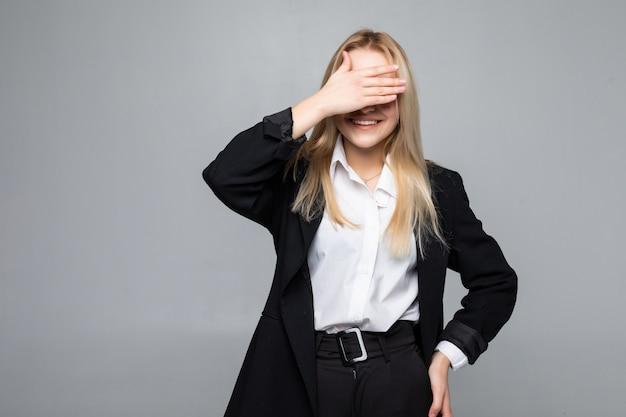 Mujer de negocios joven que cubre los ojos con las manos en la pared gris aislada