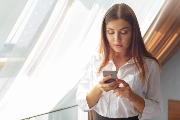 Mujer de negocios joven que habla con el teléfono en el hotel.