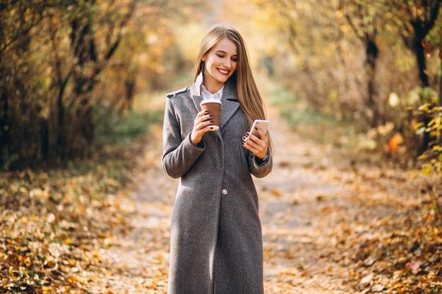Mujer de negocios joven que habla en el teléfono y que bebe el café
