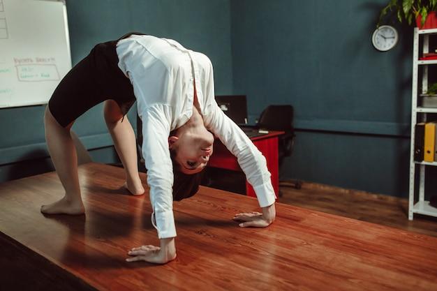 Mujer de negocios joven que hace ejercicio de puente en el escritorio de oficina