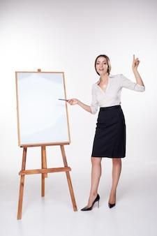 Mujer de negocios joven que muestra algo en la pared blanca