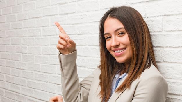 Mujer de negocios joven que señala al lado con el dedo