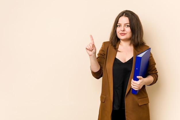 Mujer de negocios joven que sostiene los archivos que muestran el número uno con el dedo