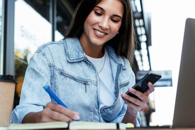 Mujer de negocios joven que trabaja en casa con terraza abierta, sentado frente a la computadora portátil, tomando notas en el cuaderno negro.