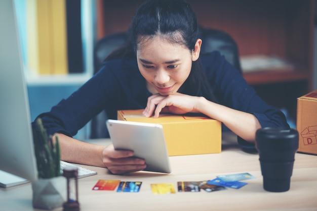 Mujer de negocios joven que trabaja compras en línea en su hogar