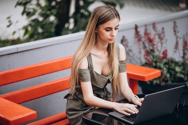 Mujer de negocios joven que trabaja en la computadora portátil afuera en un café