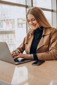 Mujer de negocios joven que trabaja en la computadora portátil en un café