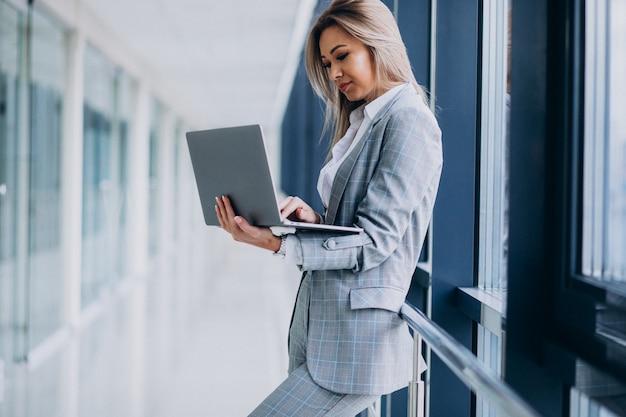 Mujer de negocios joven que trabaja en la computadora portátil en una computadora
